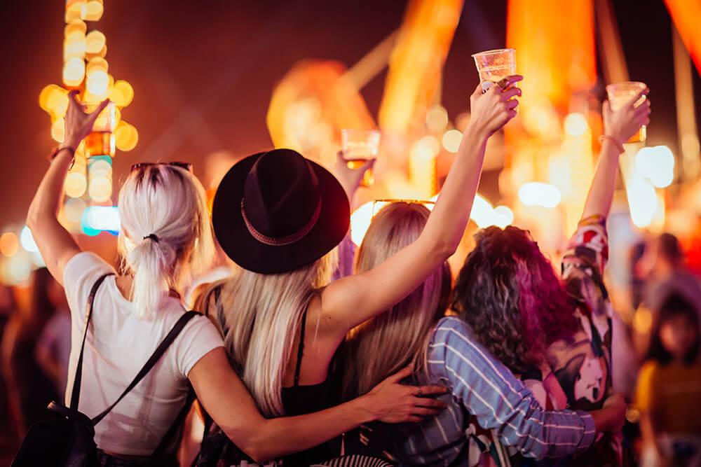 Aufnahme von vier feiernden Frauen auf einem Fest von der Kamera abgewandt