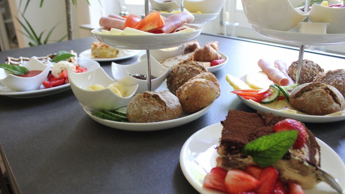 Frühstücksangebot mit Waffeln, Brötchen und Kuchen